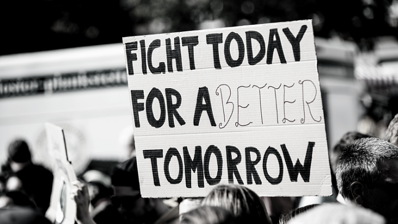 """Image of a protester holding a sign reading """"fight today for a better tomorrow"""""""
