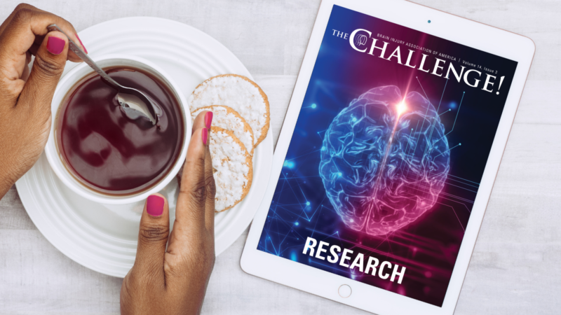 top-down shot of The Challenge Research issue shown on iPad. Black woman's hands holding coffee cup next to ipad.