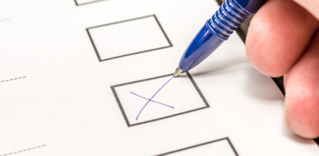 Person marking x in checkbox on a voting form