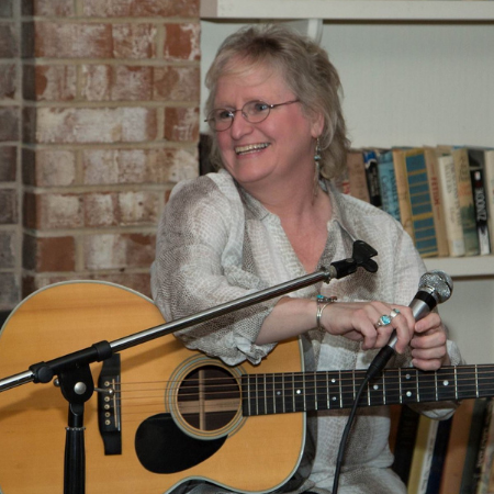 BIAA Champion Cathy Grochowski playing guitar and holding a microphone.
