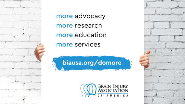 person holding poster that says more advocacy more research more education more services. biausa.org slash donate. BIAA logo bottom right.
