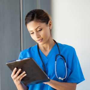 Woman in scrubs holding a clipboard and wearing a stethoscope