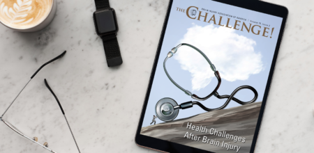 The Challenge Vol. 15 Iss. 2 on Health Challenges displayed on iPad laying on marble table next to cappuccino and glasses.