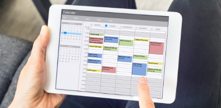 Person looking at weekly schedule on a tablet