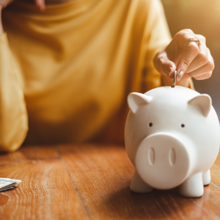 Individual wearing a yellow shirt dropping a coin in to a white piggy bank