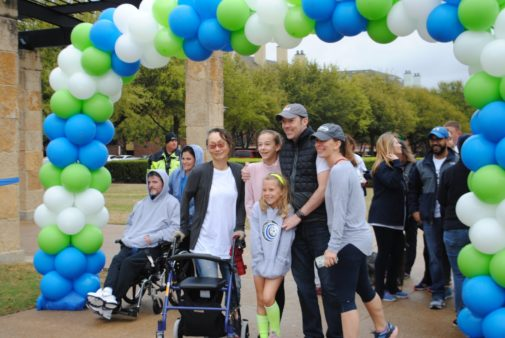 Texas Walk attendees standing under a blue, white, and green balloon arch
