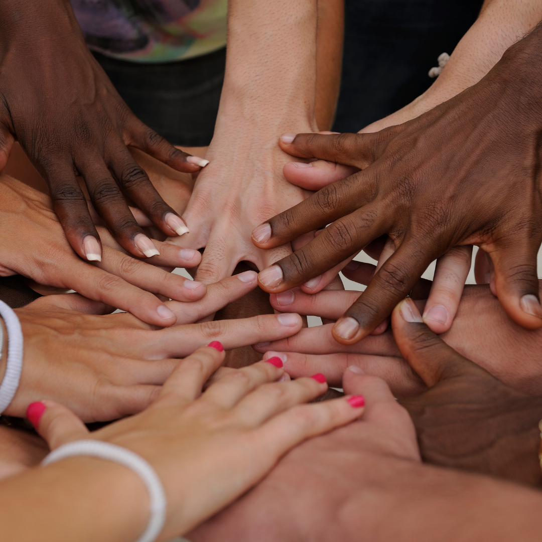 Hands from people of all races stacked together