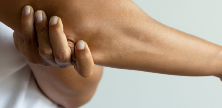 person gripping elbow on right arm
